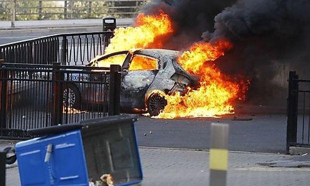 A burning car set alight during the second night of civil disturbances in central Birmingham, England