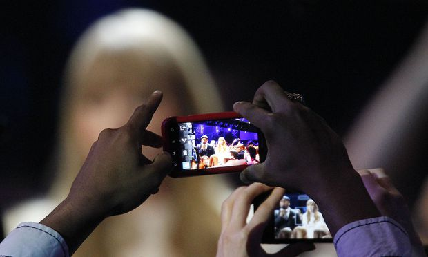 Fans take photos of Taylor Swift and LL Cool J with their cell phones as they host the Grammy Nominations Concert in Nashville