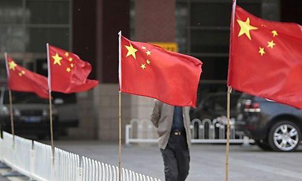 A man walks past Chinese national flags at Chaoyang Hospital, where blind activist Chen Guangcheng wa