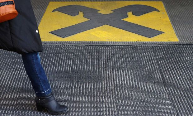 A woman walks by a Raiffeisen logo painted on the ground in front of an office building in Vienna