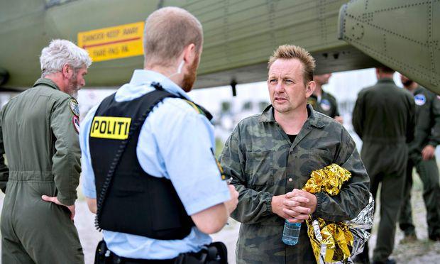 Peter Madsen (re.) nach seiner Bergung im Gespräch mit einem Polizisten. / Bild: (c) APA/AFP/Scanpix Denmark/BAX LIND