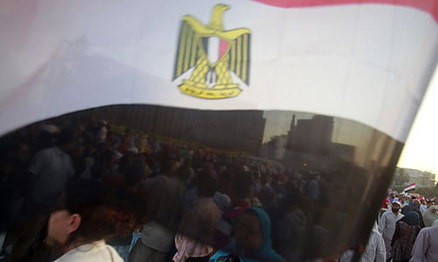 Protesters are seen through an Egyptian flag as they gather to protest against presidential candidate