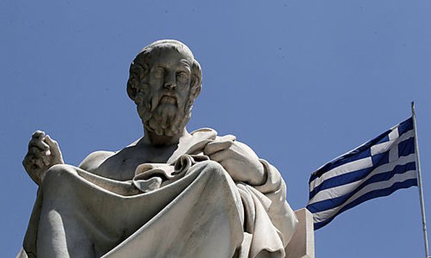 The marble statues of ancient Greek philosophers Plato, stand in front of the Athens Academy, as the