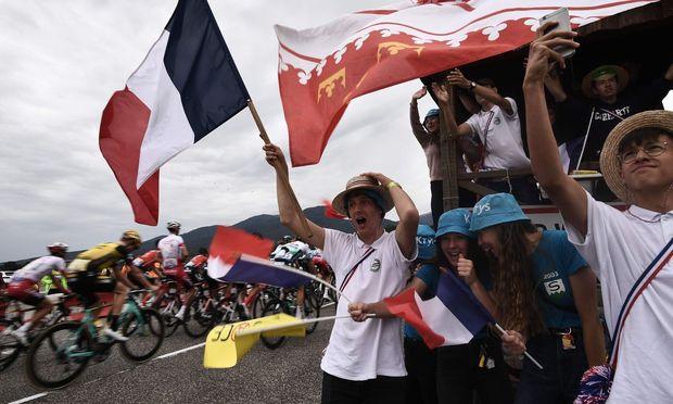 Klassisches Tour- Bild: Die Fahrer quälen sich bergauf, die Fans feiern.