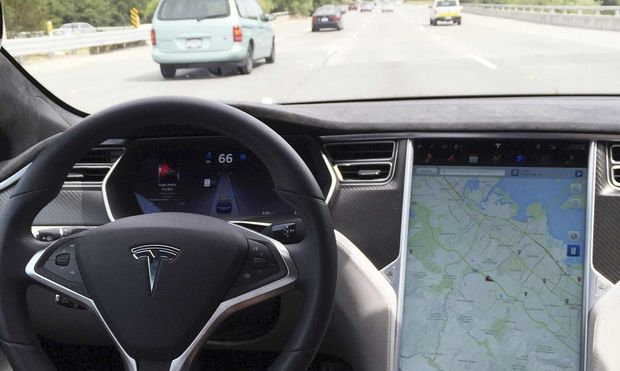 The interior of a Tesla Model S is shown in autopilot mode in San Francisco