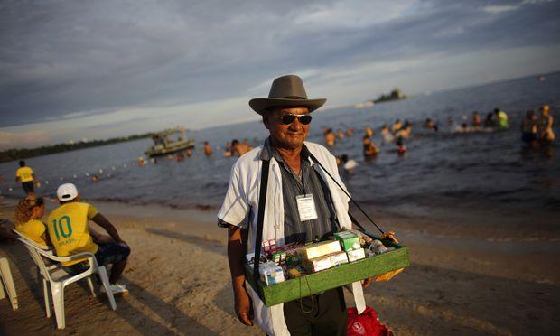 A street vendor strolls in a beach in Manaus