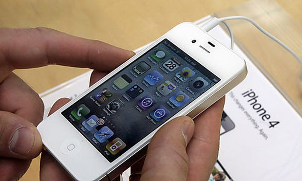 FILE - In this April 28, 2011 photo, a customer holds an iPhone at the Apple store on New York's Uppe