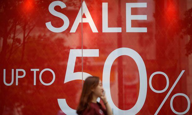 A woman walks past a sale sign
