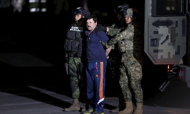 Recaptured drug lord Joaquin 'El Chapo' Guzman is escorted by soldiers during a presentation in Mexico City