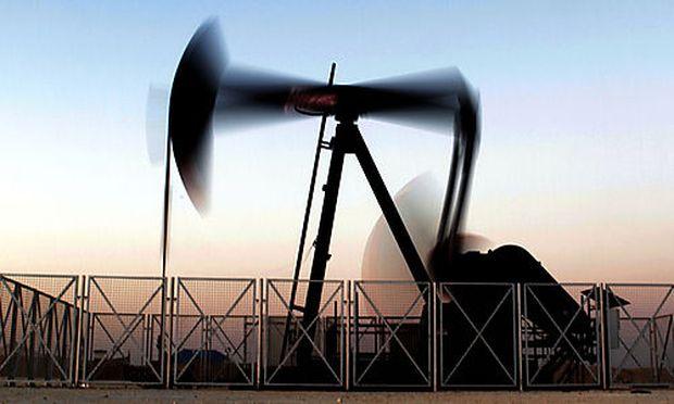 An oil pump works at sunset Tuesday, Feb. 21, 2012, in the desert oil fields of Sakhir, Bahrain.  Oil