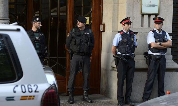 Zivilgardisten (li.) und Mossos d'Esquadra vor dem Wirtschaftsministerium in Barcelona