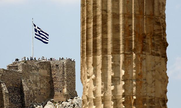 Greek flag flutters atop the Acropolis hill in Athens, Greece