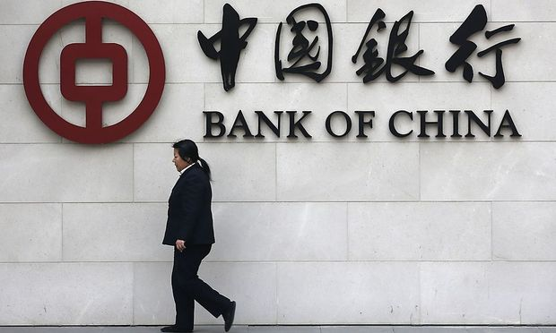File photo of a woman walking past a sign of Bank of China at its branch in Beijing