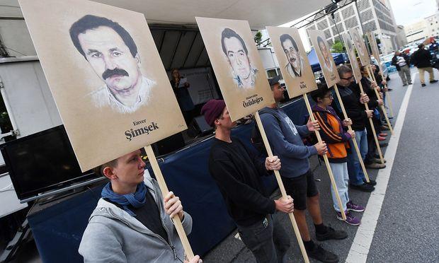 Demonstranten halten bei einer Kundgebung vor dem Oberlandesgericht Schilder mit Abbildungen der NSU-Opfer.