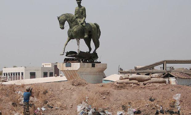 Ein kudischer Kämpfer feuert auf eine Statue von Bassel al-Assad, dem Bruder des syrischen Präsidenten.