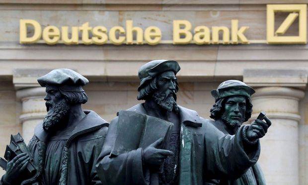 FILE PHOTO: A statue is pictured next to the logo of Germany´s Deutsche Bank in Frankfurt