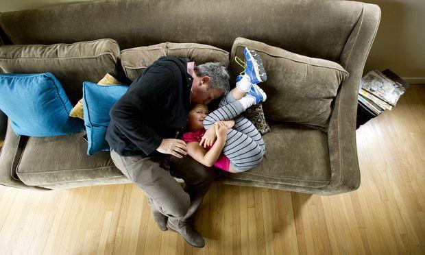Tobendes Spielen fördert die Bindung von Vater und Kind. Kuscheln senkt für einige Zeit das Testosteron des Vaters.