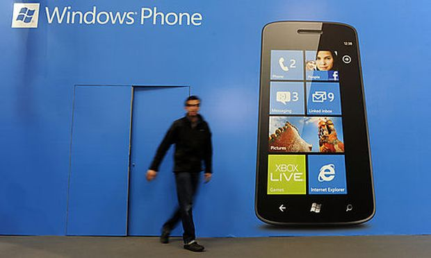A man walks past a banner of a Windows phone at the Mobile World Congress, the worlds largest mobile