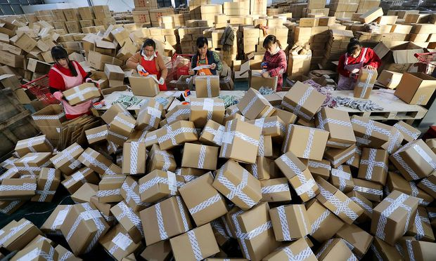 GANYU CHINA NOVEMBER 11 Workers distribute packs a logistics centre of China Post during Alibaba