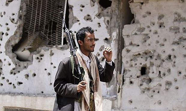 A tribal fighter loyal to Sadiq al-Ahmar, the leader of the Hashed tribe, walks in front of a bullet-