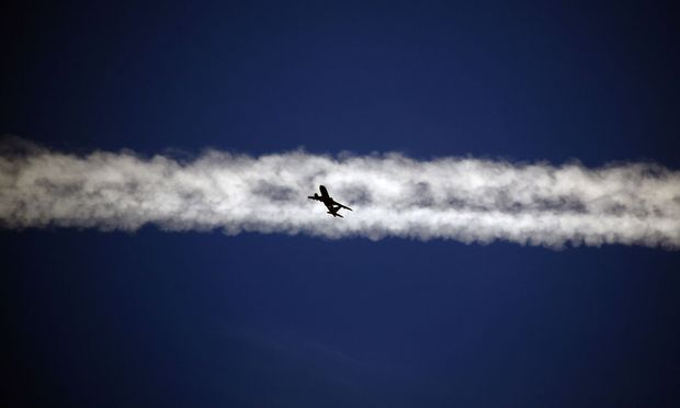 An aeroplane flies underneath the jet stream of another aircraft above the Italian city of Padova