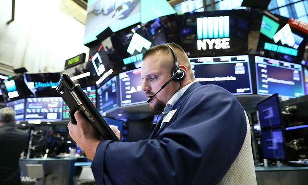 A trader works on the floor of the New York Stock Exchange (NYSE) near the close of market in New York