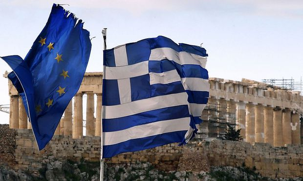 A Greek and an EU flag fly over the Greek ministry of finance in Athens