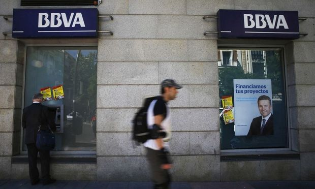 A man uses an ATM machine at a BBVA bank branch in Madrid