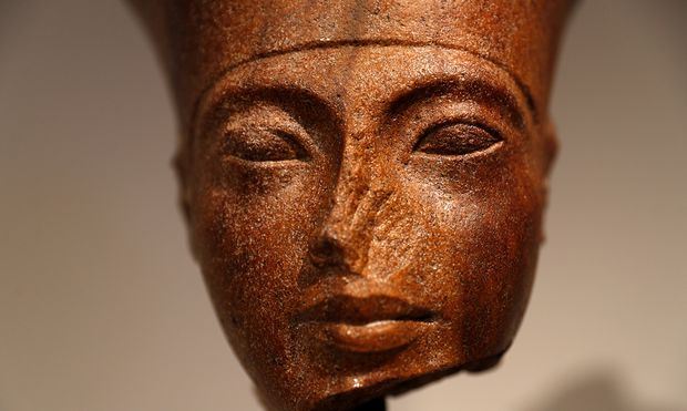 An Egyptian brown quartzite head of the God Amen is seen at Christie´s auction house prior to its´ sale in London