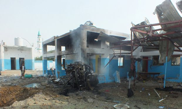 A dead body is seen at the site of a Saudi-led air strike on a hospital in Abs district