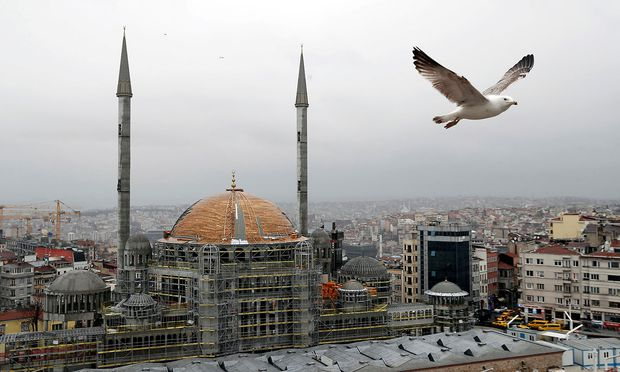 FILE PHOTO: A seagull flies over the Taksim sqaure with a new mosque under construction in the background, in central Istanbul