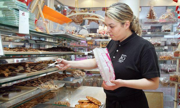 Auszubildende zur Fachverkaeferin im Lebensmittel Handwerk verpackt in einer Konditorei Gebaeck