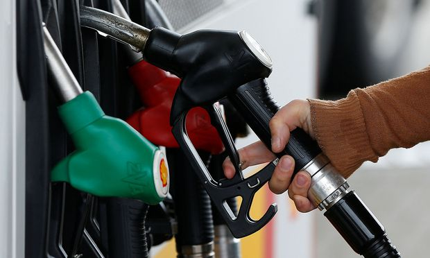 A customer prepares to fill the tank of her car at a fuel station in Sint Pieters Leeuw