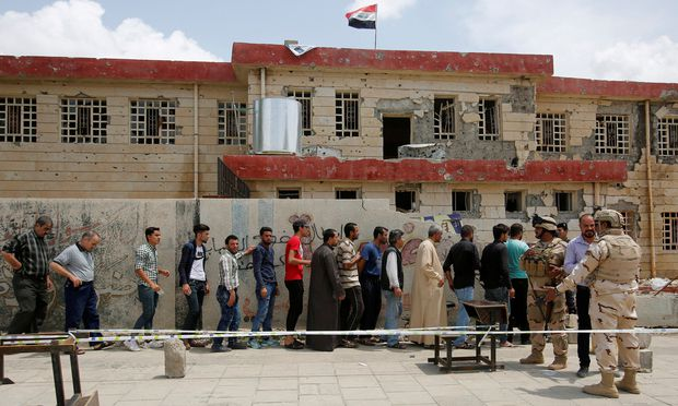 Iraqi people stand in a queue to cast their vote at a polling station during the parliamentary election in Mosul