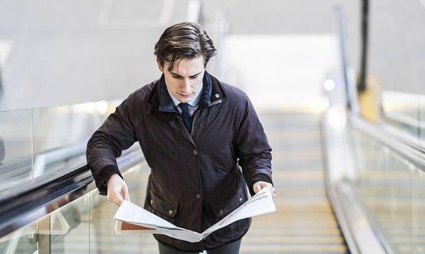 Businessman on escalator reading a newspaper model released Symbolfoto PUBLICATIONxINxGERxSUIxAUTxHU