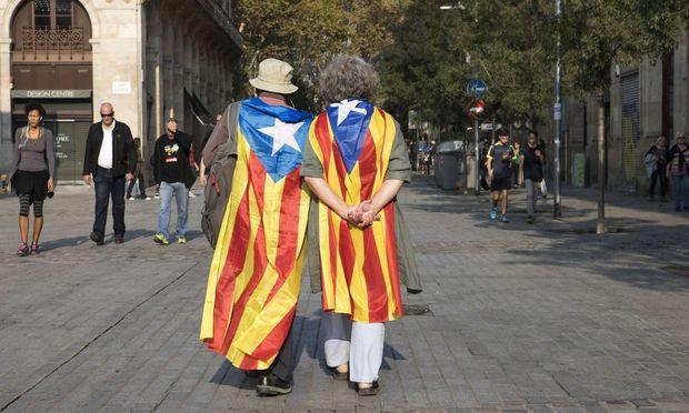 Die Ruhe vor dem nächsten Sturm? Katalanische Unabhängigkeitsaktivisten schlendern durch die Straßen Barcelonas.