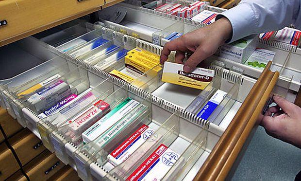 ** ARCHIV ** Ein Apotheker nimmt Medikamente aus der Schublade eines Apothekenschranks, fotografiert
