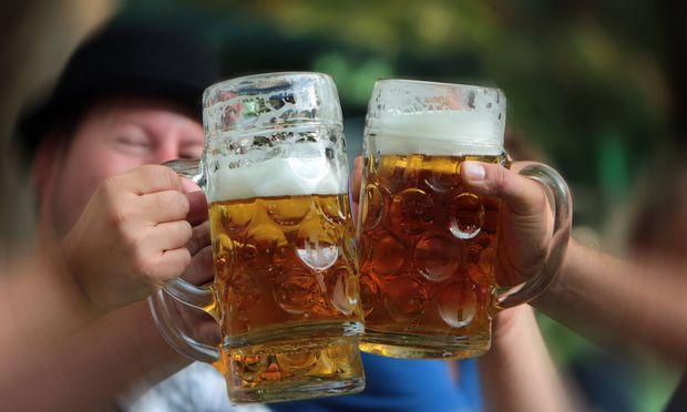gemeinsames Zuprosten und Ansto�en mit einer Mass Bier im Biergarten in M�nchen Bayern Deutschland
