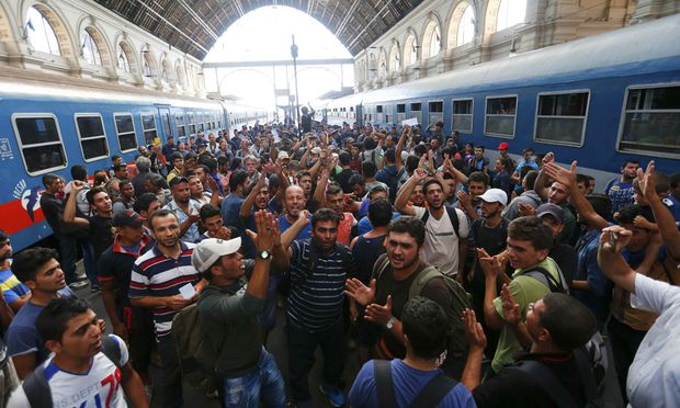 Migrants gesture as they stand in the main Eastern Railway station in Budapest