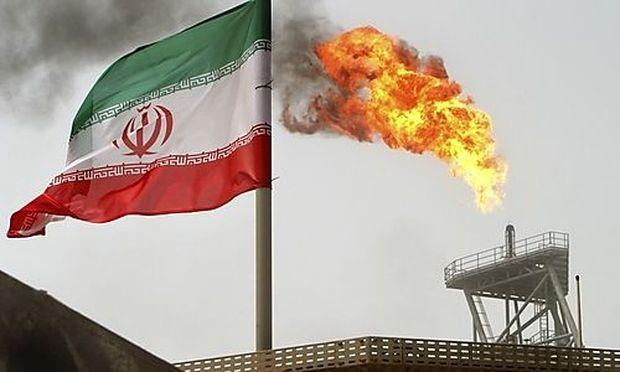 Die iranische Flagge vor einer Ölplattform im persischen Golf