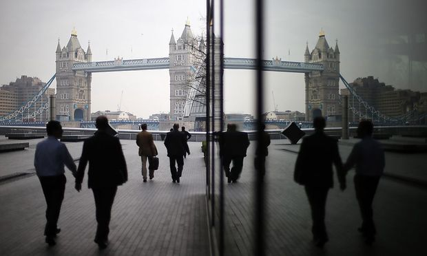Pedestrians are reflected in glass fronted office buildings as they walk towards Tower Bridge on the south bank of the Thames, in central London