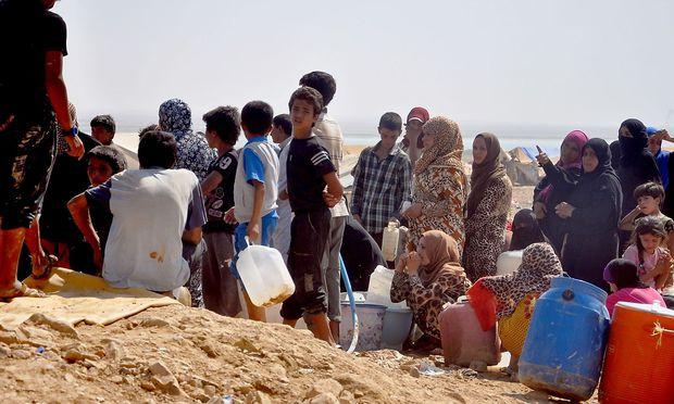 Flüchtlinge in Syrien stellen sich zum Wasserholen an.