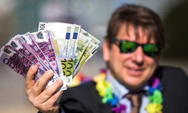 Ein Aktivist hält falsche Banknoten bei einer Demonstration vor der EU-Kommission in Brüssel in die Kamera.