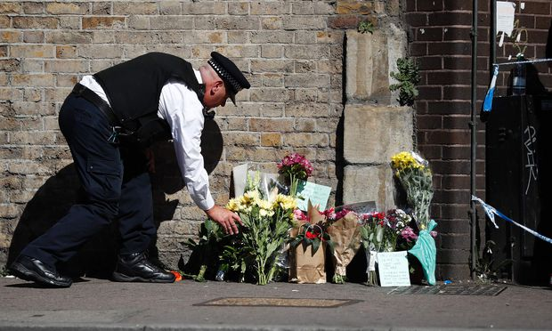 Ein Polizist legt am Anschlagsort in Finsbury Park im Norden von London Blumen nieder.