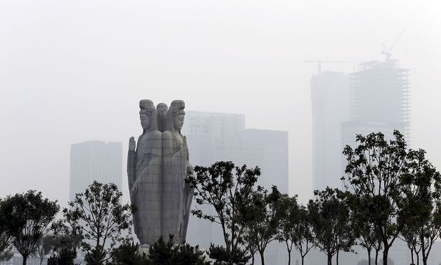 Avalokitesvara Bodhisattva statue is seen in front of buildings under construction, at Chaoyin Temple, during a hazy day in Tianjin