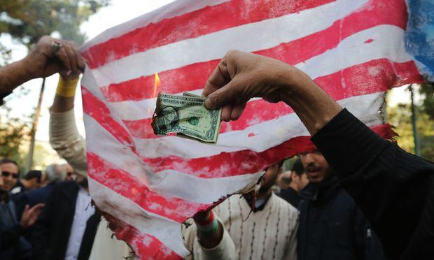 Iranische Demonstranten verbrennen Dollarscheine. Als Weltleitwährung ist der Dollar schon länger angezählt.  / Bild: (c) APA/AFP/ATTA KENARE