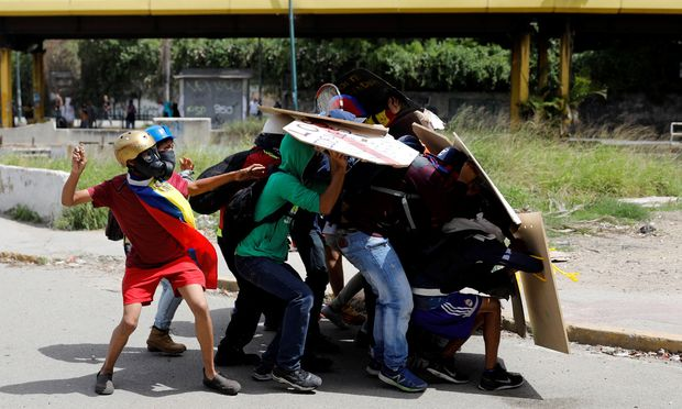 Demonstrators use shields for cover as they throw stones during a protest against Venezuela´s President Maduro´s government in Caracas