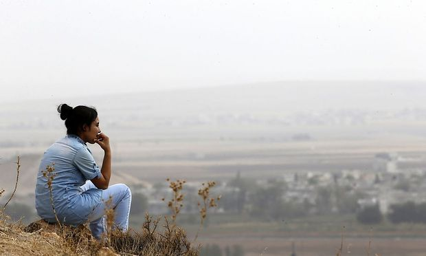 A Turkish Kurd woman watches the Syrian town of Kobani from near the Mursitpinar border crossing