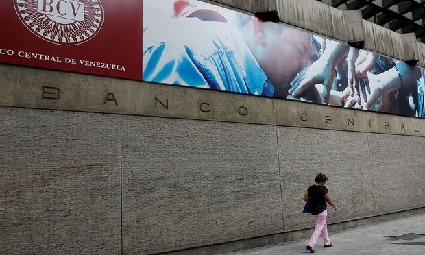 FILE PHOTO: A woman walks outside of the Venezuela's Central Bank in Caracas