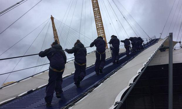 Gut gesichert auf der Außenhaut der O2 Arena herumkraxeln. Von der Themse bläst ein scharfer Wind.